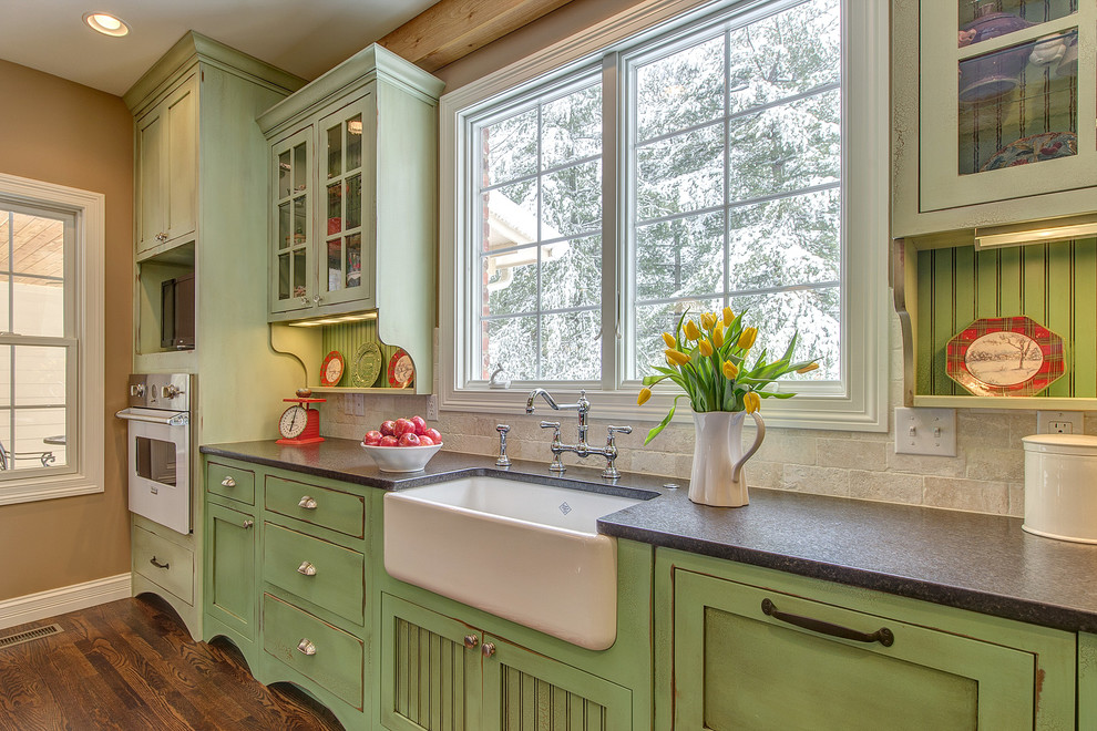 Example of a classic kitchen design in St Louis with white appliances, green cabinets and travertine backsplash
