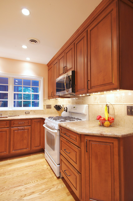 Example of a mid-sized classic l-shaped light wood floor kitchen design in Baltimore with an undermount sink, raised-panel cabinets, medium tone wood cabinets, granite countertops, beige backsplash, ceramic backsplash, white appliances and an island