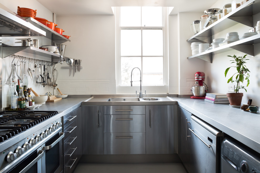 Example of a small urban u-shaped kitchen design in London with a double-bowl sink, flat-panel cabinets, stainless steel cabinets, concrete countertops, white backsplash, subway tile backsplash, stainless steel appliances and no island