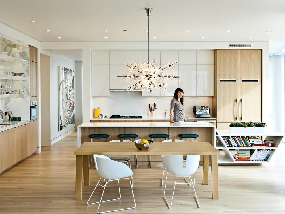 Eat-in kitchen - contemporary eat-in kitchen idea in Portland with flat-panel cabinets, light wood cabinets, paneled appliances, white backsplash and stone slab backsplash