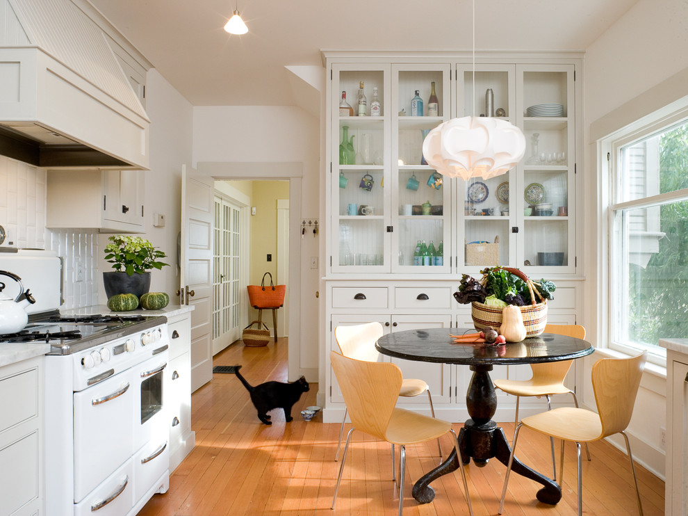 Example of a trendy enclosed kitchen design in Portland with white appliances, beaded inset cabinets, white cabinets, white backsplash and subway tile backsplash