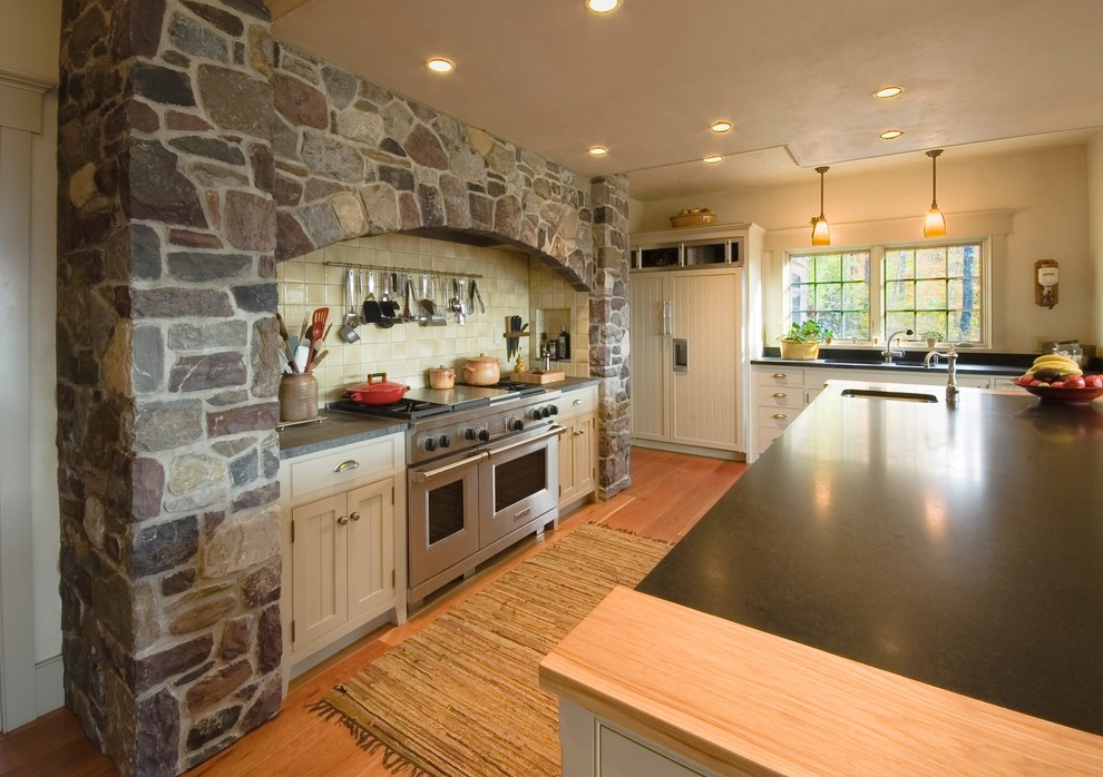 Kitchen pantry - large traditional u-shaped kitchen pantry idea in Burlington with an undermount sink, recessed-panel cabinets, granite countertops, stainless steel appliances, an island and black countertops