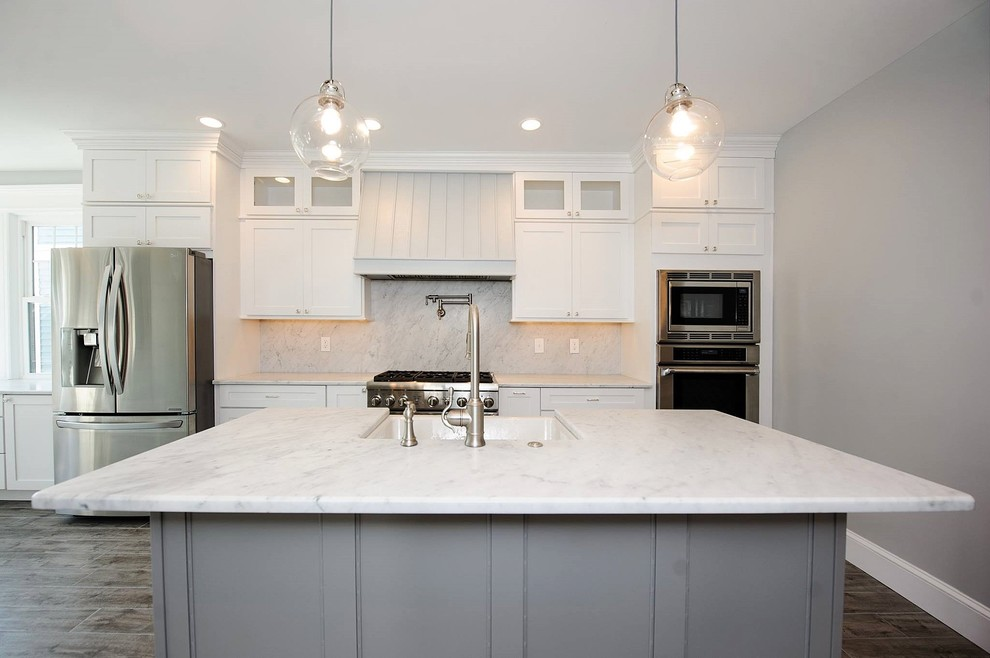 Example of a large transitional single-wall porcelain floor and brown floor eat-in kitchen design in Philadelphia with a farmhouse sink, recessed-panel cabinets, white cabinets, marble countertops, white backsplash, marble backsplash, stainless steel appliances and an island