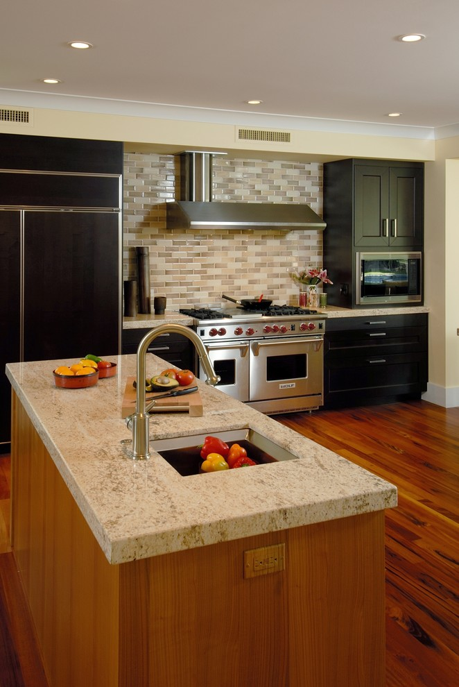 Example of a trendy kitchen design in Hawaii with stainless steel appliances, granite countertops, black cabinets and subway tile backsplash
