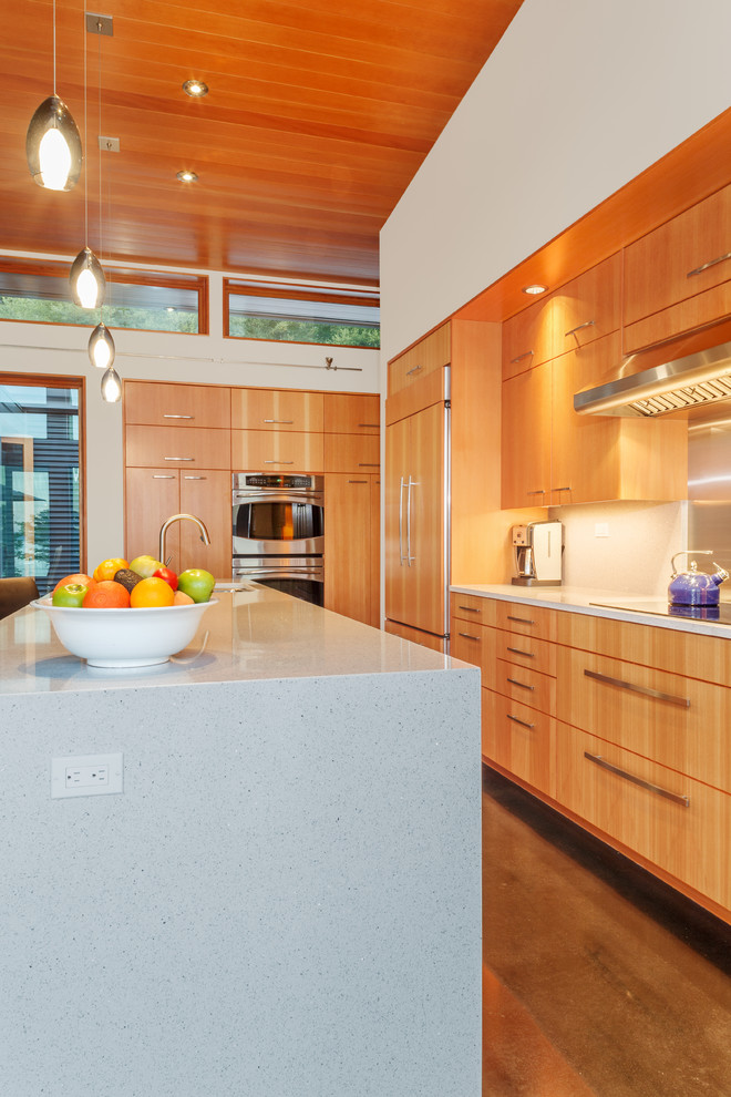 Inspiration for a small contemporary single-wall concrete floor open concept kitchen remodel in Seattle with flat-panel cabinets, medium tone wood cabinets, white backsplash, stainless steel appliances, a double-bowl sink, quartz countertops, glass sheet backsplash and an island