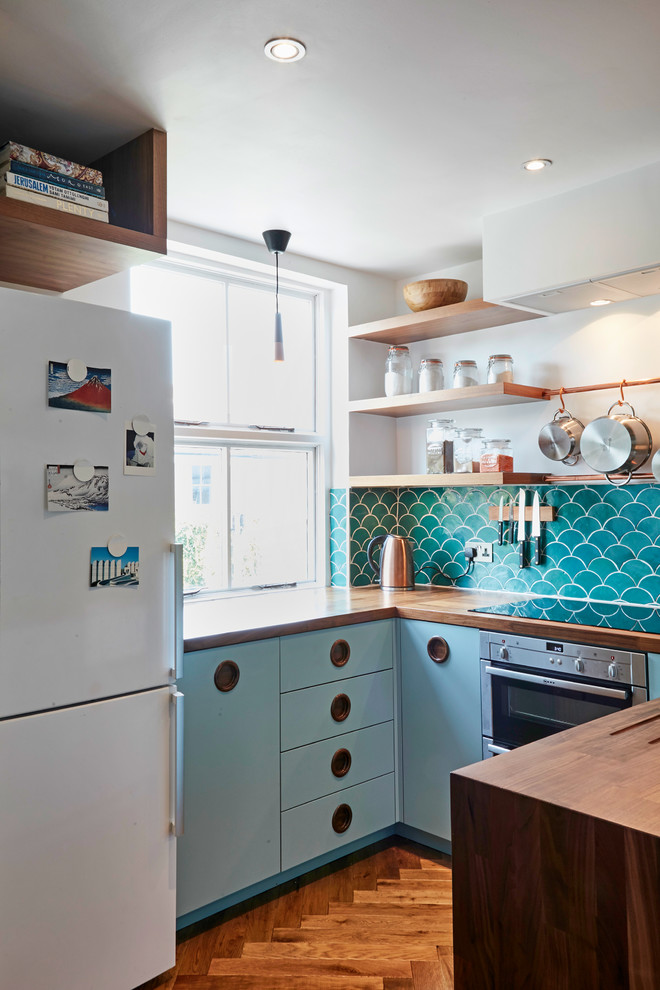 Enclosed kitchen - small 1960s u-shaped dark wood floor and brown floor enclosed kitchen idea in London with a farmhouse sink, flat-panel cabinets, blue cabinets, wood countertops, blue backsplash, cement tile backsplash, stainless steel appliances and no island