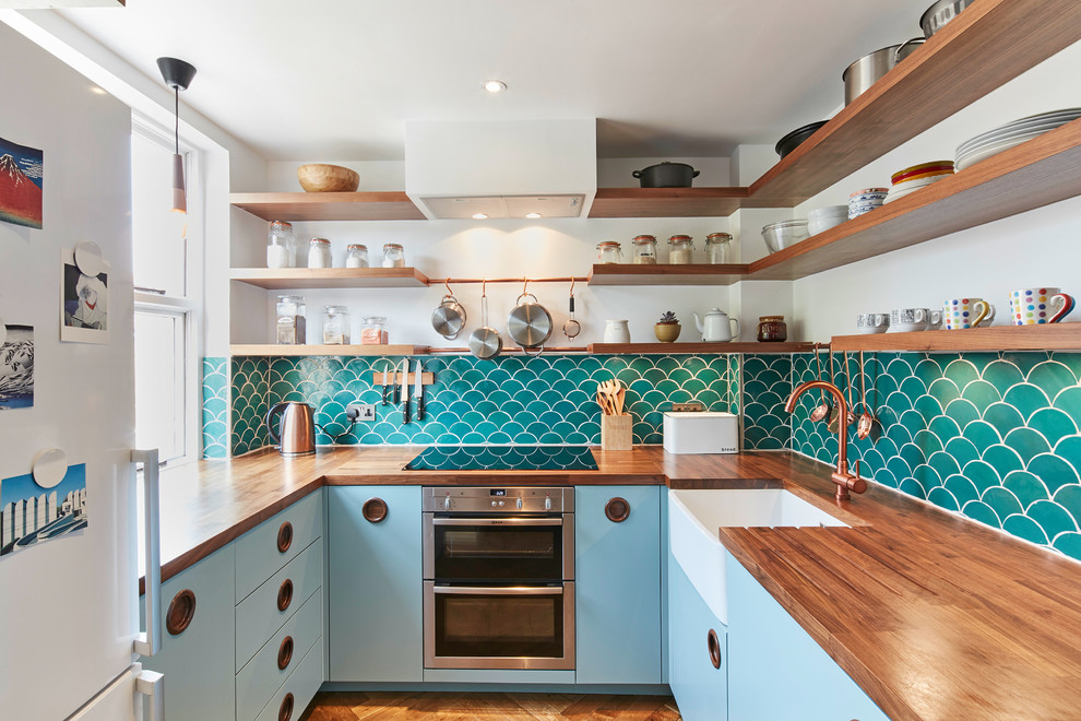 Inspiration for a small midcentury modern u-shaped medium tone wood floor and brown floor enclosed kitchen remodel in London with a farmhouse sink, flat-panel cabinets, blue cabinets, wood countertops, stainless steel appliances, no island, green backsplash and ceramic backsplash