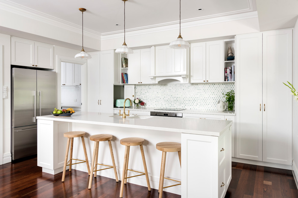 Inspiration for a mid-sized beach style l-shaped open plan kitchen in Perth with a double-bowl sink, shaker cabinets, white cabinets, multi-coloured splashback, stainless steel appliances, dark hardwood floors, an island and brown floor.