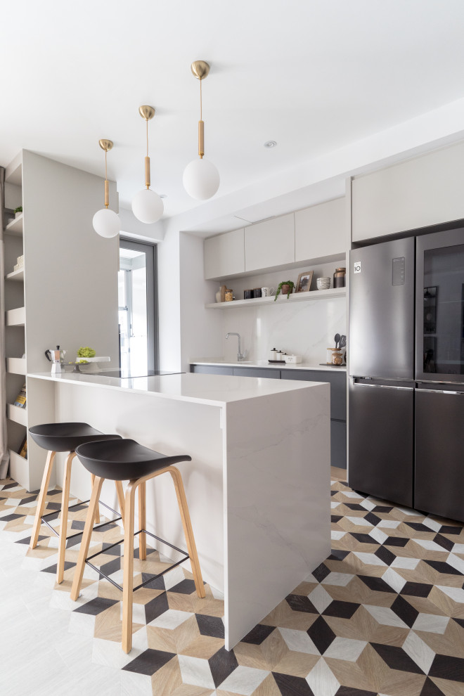 Kitchen - contemporary galley multicolored floor kitchen idea in Singapore with flat-panel cabinets, gray cabinets, black appliances, a peninsula and white countertops