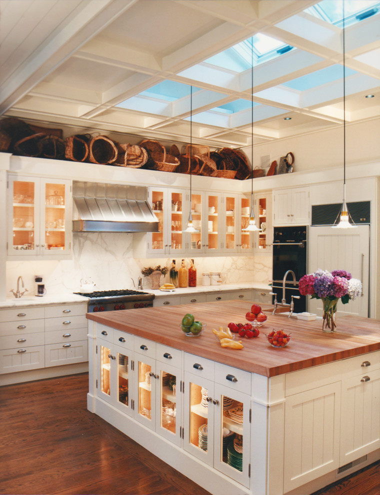 Inspiration for a timeless kitchen remodel in San Francisco with glass-front cabinets, white cabinets, white backsplash, black appliances and marble backsplash