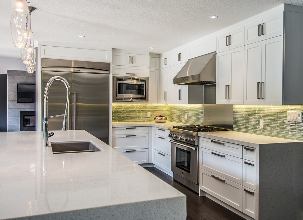 Eat-in kitchen - contemporary u-shaped eat-in kitchen idea in Toronto with an undermount sink, shaker cabinets, white cabinets, quartz countertops, green backsplash, glass sheet backsplash and stainless steel appliances