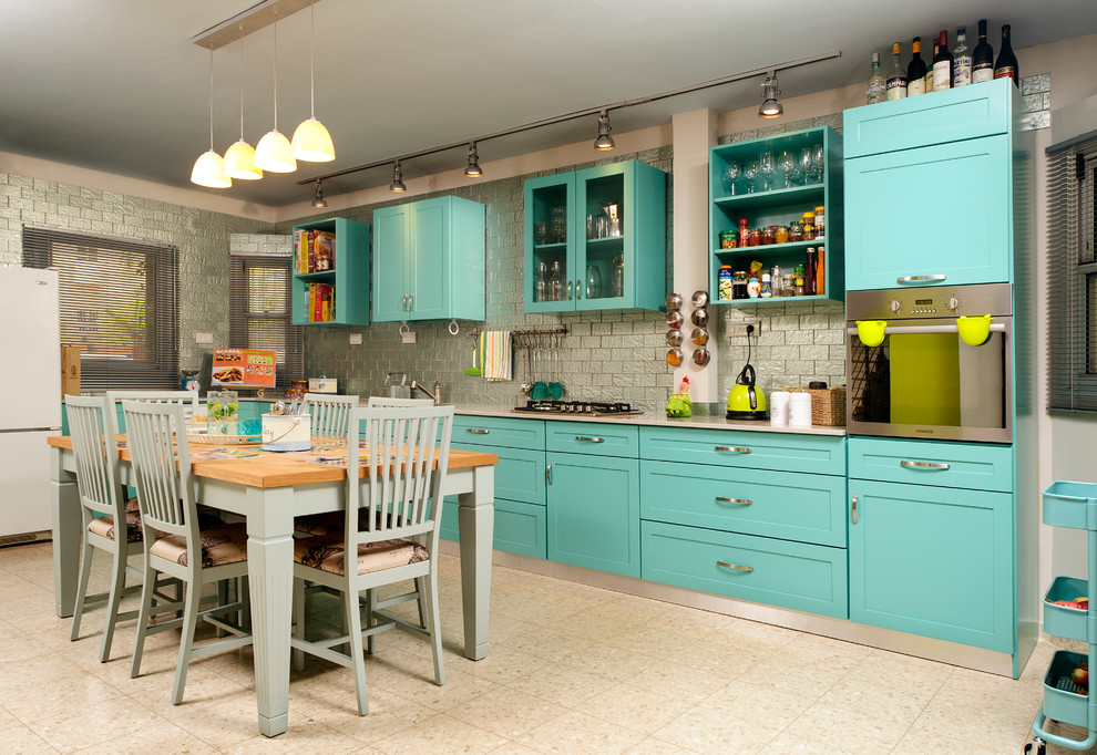 Example of an eclectic kitchen design in Tel Aviv with blue cabinets and subway tile backsplash
