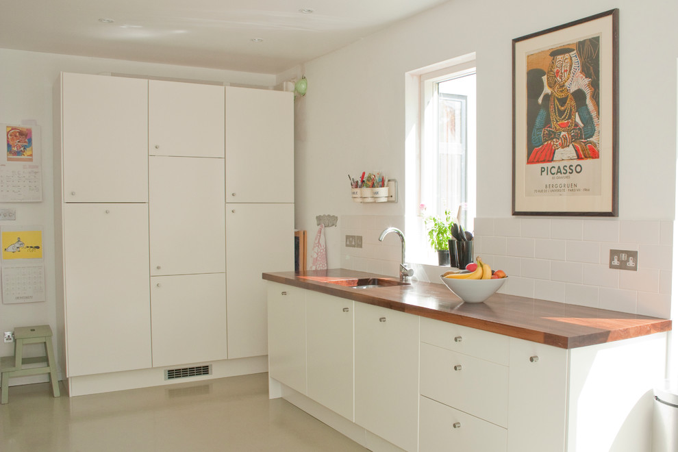 Inspiration for a contemporary beige floor kitchen remodel in Other with wood countertops, flat-panel cabinets, white cabinets, an undermount sink, white backsplash and subway tile backsplash
