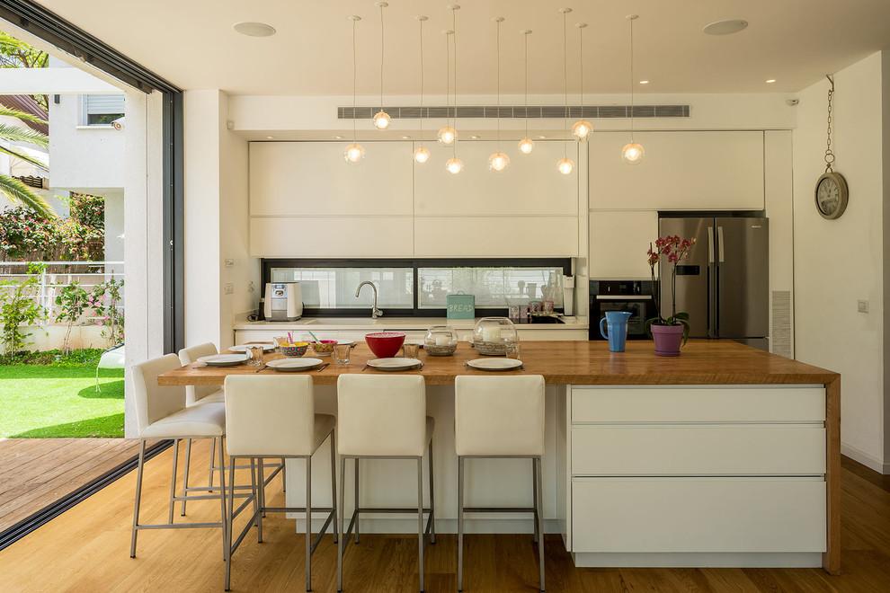 Cette image montre une petite cuisine ouverte parallèle minimaliste avec un placard à porte plane, des portes de placard blanches, un plan de travail en bois, un électroménager en acier inoxydable, un îlot central, un évier 1 bac et un sol en bois brun.