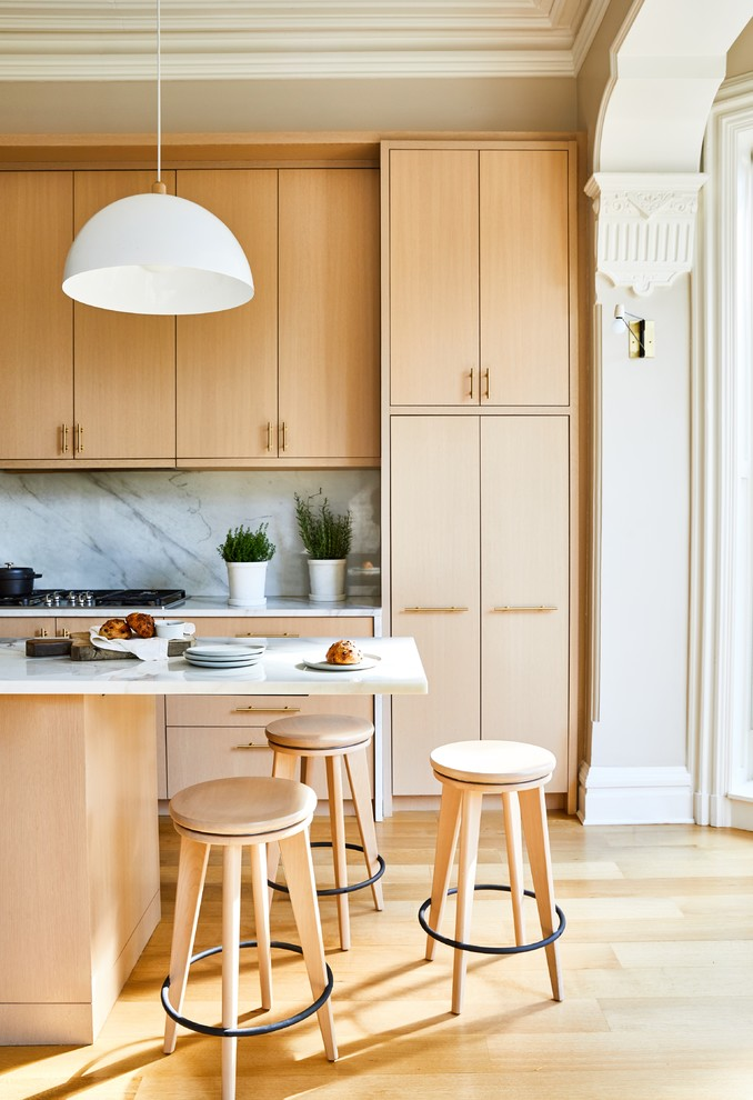 Example of a transitional light wood floor and beige floor kitchen design in New York with flat-panel cabinets, light wood cabinets, white backsplash, stone slab backsplash, an island and white countertops
