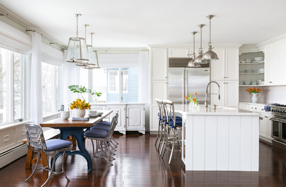 Inspiration for a large coastal dark wood floor eat-in kitchen remodel in New York with shaker cabinets, white cabinets, stainless steel appliances and an island