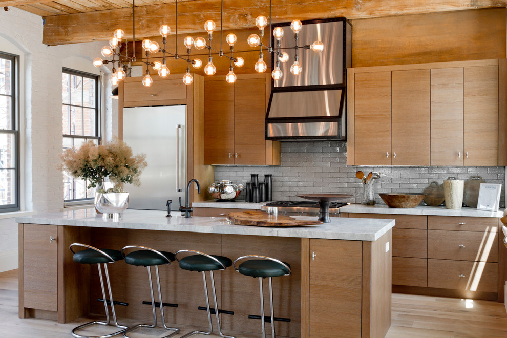 Example of a trendy galley light wood floor kitchen design in New York with flat-panel cabinets, medium tone wood cabinets, gray backsplash and an island