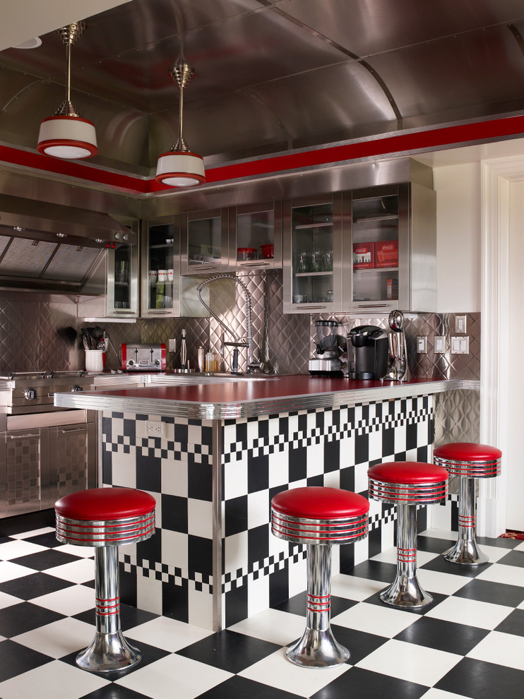 Eclectic kitchen photo in New York with metallic backsplash, stainless steel appliances and red countertops
