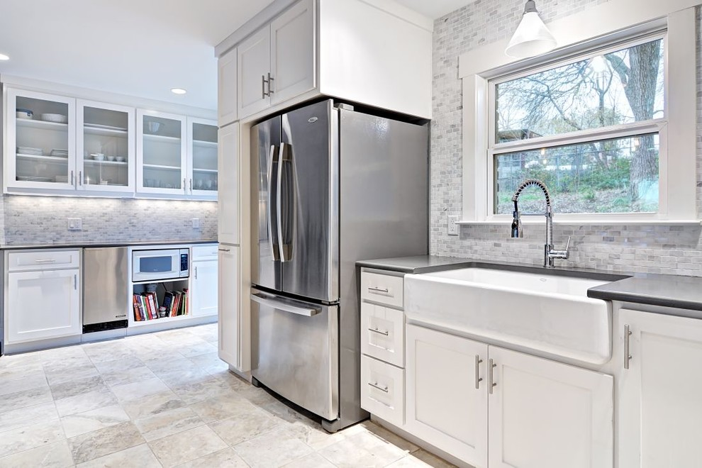 Example of a trendy kitchen design in Austin with stone tile backsplash, stainless steel appliances, a farmhouse sink, white backsplash, white cabinets and shaker cabinets