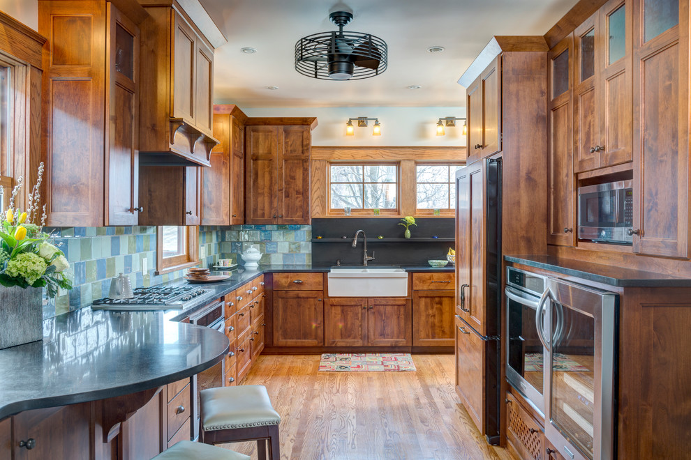 Inspiration for a craftsman medium tone wood floor kitchen remodel in Kansas City with recessed-panel cabinets, medium tone wood cabinets, blue backsplash and stainless steel appliances