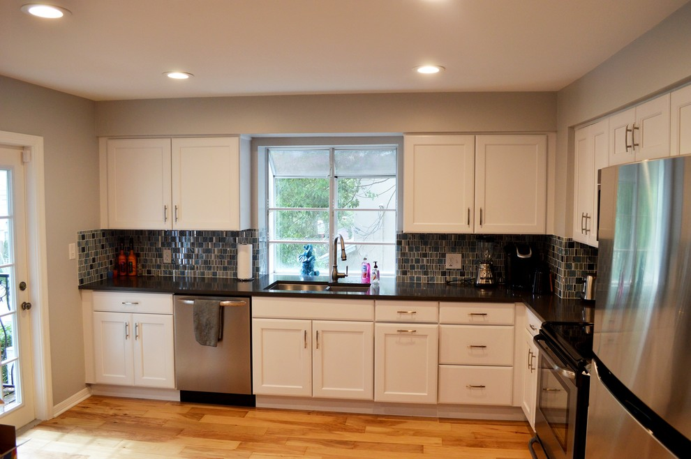 Small trendy l-shaped light wood floor enclosed kitchen photo in Tampa with an undermount sink, recessed-panel cabinets, white cabinets, quartz countertops, blue backsplash, glass tile backsplash, stainless steel appliances and no island