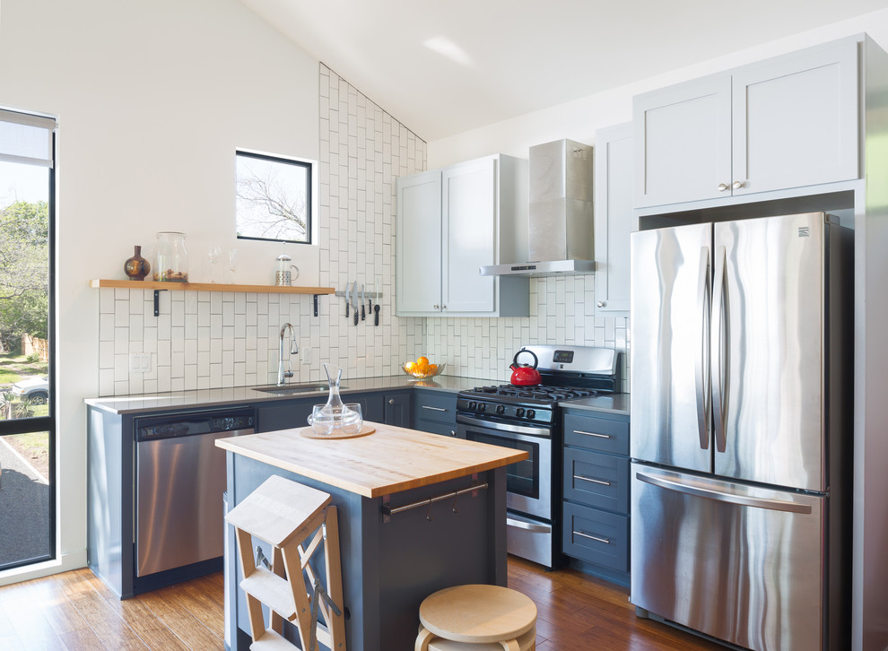 Kitchen - small transitional l-shaped medium tone wood floor and orange floor kitchen idea in Austin with an undermount sink, soapstone countertops, white backsplash, subway tile backsplash, stainless steel appliances, an island, shaker cabinets and blue cabinets