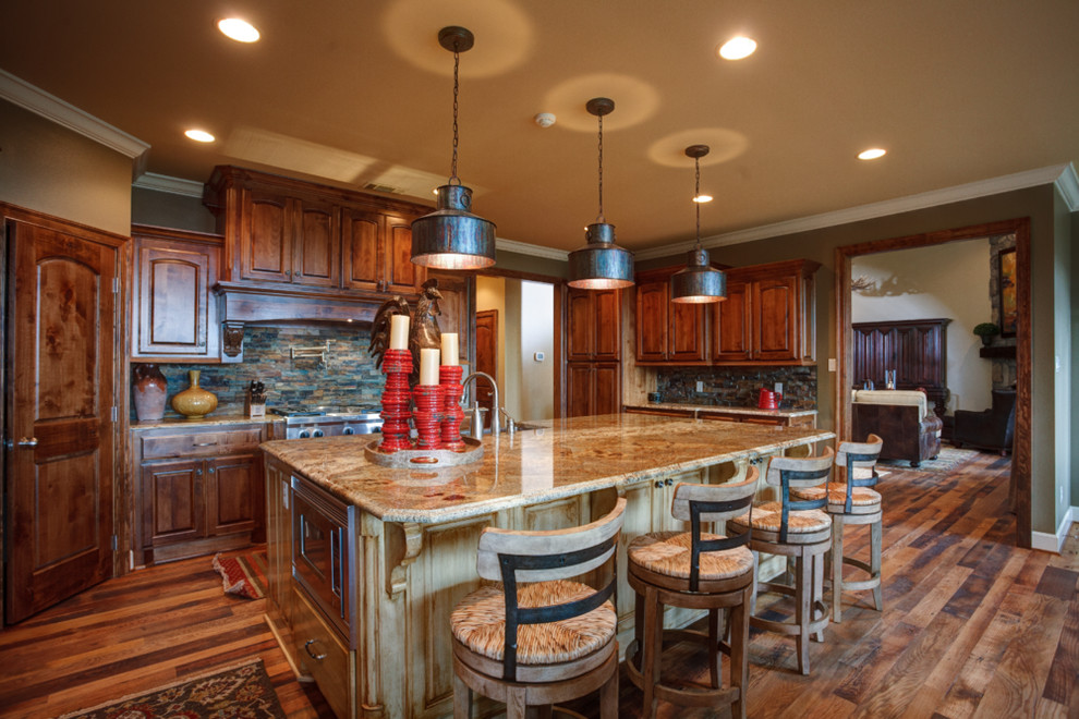 Mid-sized mountain style u-shaped dark wood floor and brown floor open concept kitchen photo in Little Rock with a farmhouse sink, raised-panel cabinets, dark wood cabinets, granite countertops, multicolored backsplash, stone tile backsplash, stainless steel appliances and an island