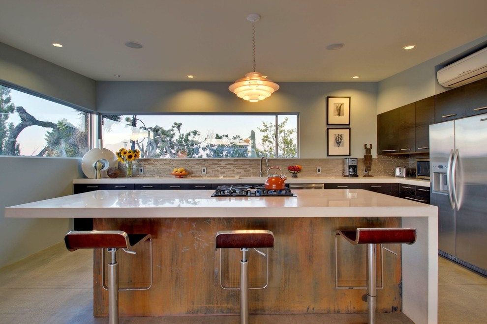 1950s u-shaped concrete floor eat-in kitchen photo in Los Angeles with flat-panel cabinets, dark wood cabinets, beige backsplash, stainless steel appliances and an island