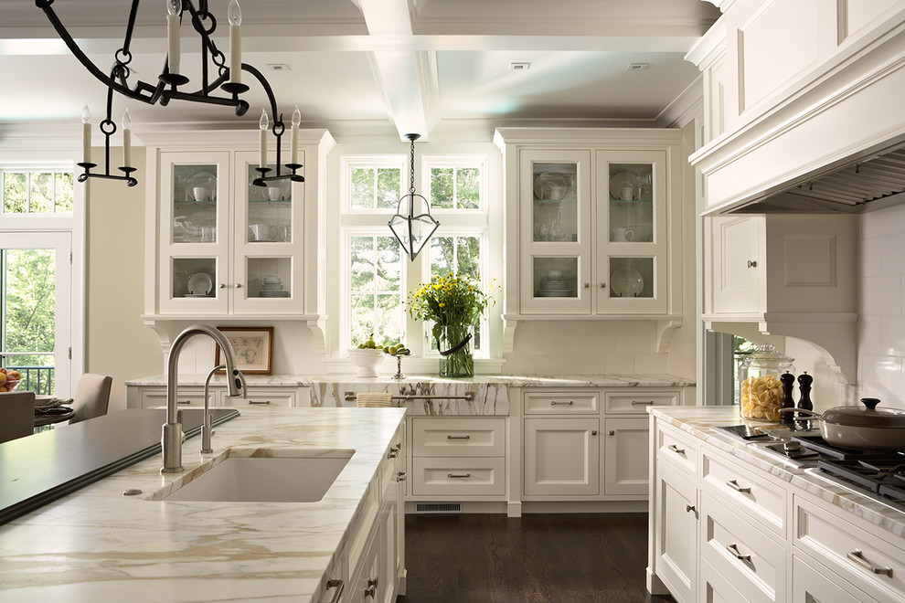 Large transitional u-shaped dark wood floor open concept kitchen photo in Minneapolis with a single-bowl sink, glass-front cabinets, white cabinets, marble countertops, white backsplash, ceramic backsplash, paneled appliances and an island