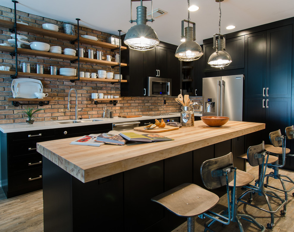 Example of a small urban l-shaped light wood floor and brown floor kitchen design in Miami with a double-bowl sink, shaker cabinets, black cabinets, wood countertops, stainless steel appliances, an island, red backsplash, brick backsplash and white countertops