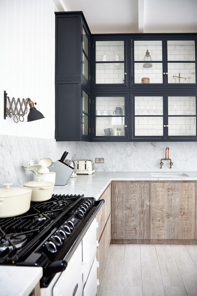 Inspiration for a scandinavian l-shaped light wood floor kitchen remodel in London with an undermount sink, glass-front cabinets, black cabinets, marble countertops, white backsplash, stone slab backsplash and white appliances