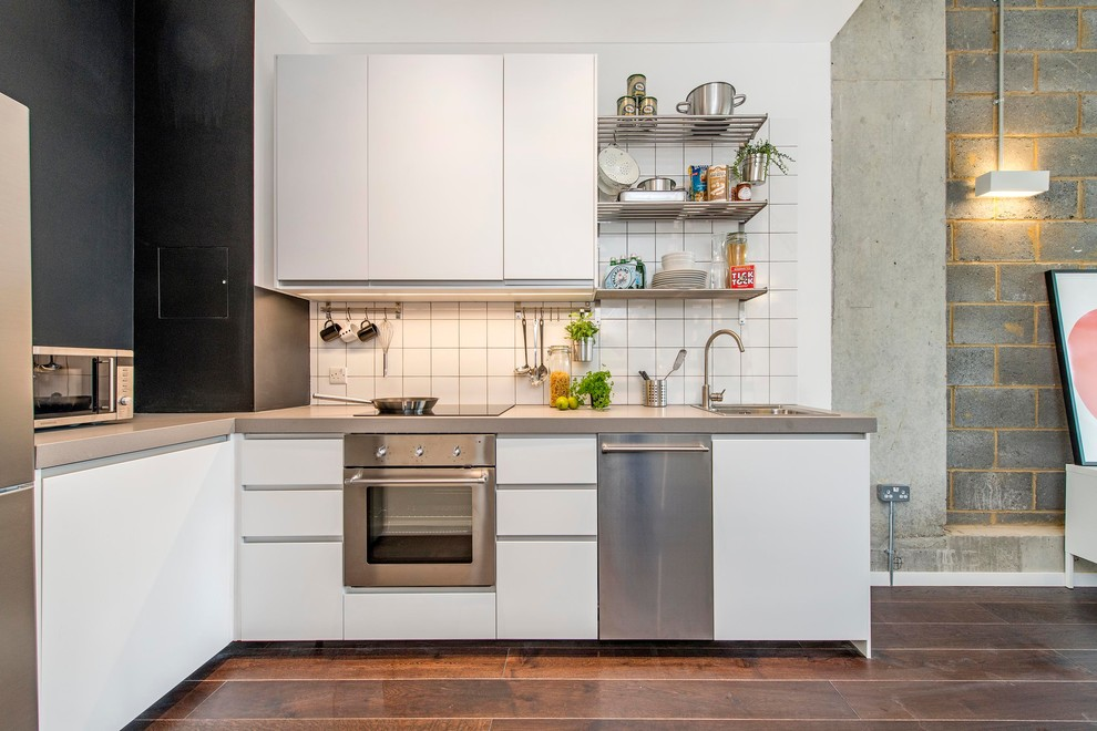 Open concept kitchen - small industrial l-shaped dark wood floor open concept kitchen idea in London with a drop-in sink, flat-panel cabinets, white cabinets, concrete countertops, white backsplash, ceramic backsplash, stainless steel appliances and no island