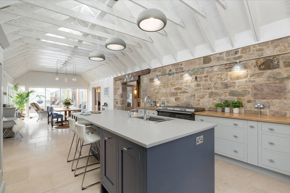 Inspiration for a large farmhouse travertine floor eat-in kitchen remodel in Other with flat-panel cabinets, gray cabinets, quartzite countertops, stainless steel appliances, an island and an undermount sink
