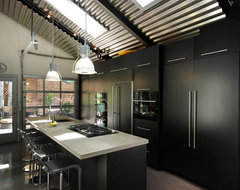 Contemporary black kitchen with concrete counters and stainless steel fixtures industrial-kitchen