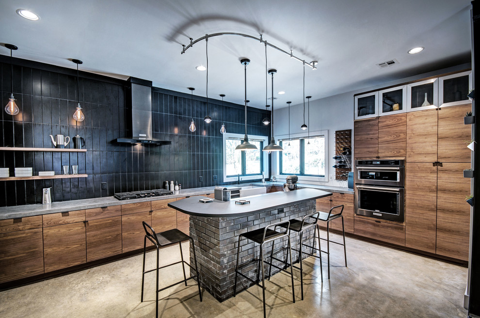 Example of an urban l-shaped gray floor kitchen design in Jackson with a farmhouse sink, flat-panel cabinets, brown cabinets, black backsplash, subway tile backsplash, an island and gray countertops
