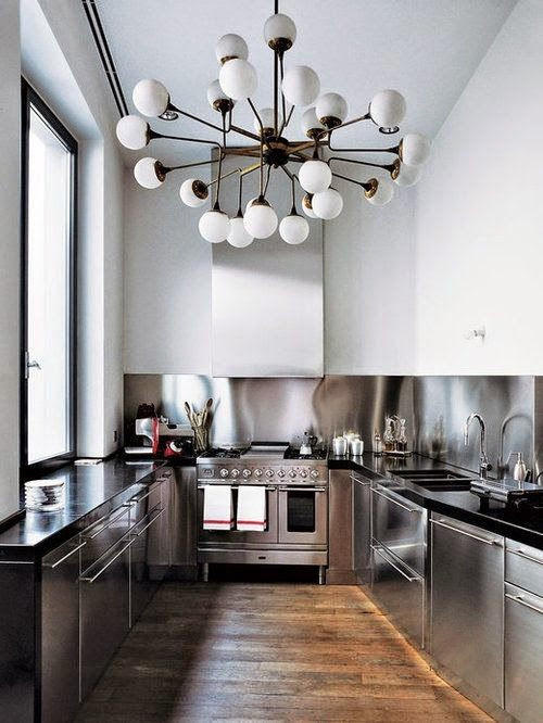 Inspiration for a mid-sized industrial u-shaped medium tone wood floor and brown floor eat-in kitchen remodel in Columbus with an undermount sink, flat-panel cabinets, stainless steel cabinets, granite countertops, metallic backsplash, stainless steel appliances and black countertops