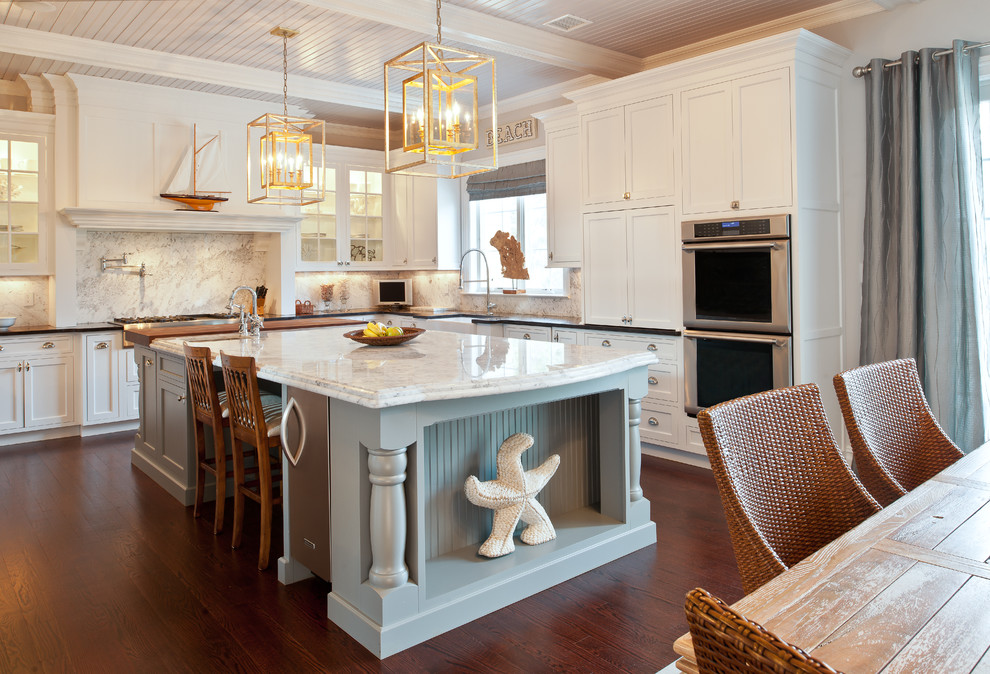 Enclosed kitchen - mid-sized traditional u-shaped dark wood floor enclosed kitchen idea in New York with shaker cabinets, a farmhouse sink, white cabinets, marble countertops, white backsplash, stone slab backsplash, stainless steel appliances and an island