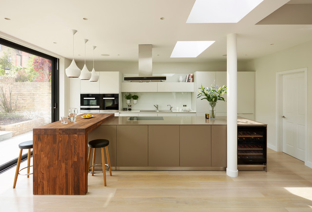 This is an example of a contemporary single-wall kitchen in London with flat-panel cabinets, white cabinets, white splashback, stainless steel appliances, light hardwood flooring and an island.
