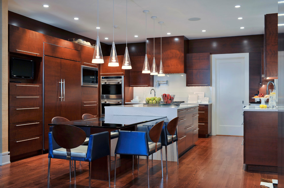 Inspiration for a contemporary u-shaped medium tone wood floor and brown floor kitchen remodel in Miami with flat-panel cabinets, dark wood cabinets, white backsplash, stainless steel appliances, an island and gray countertops