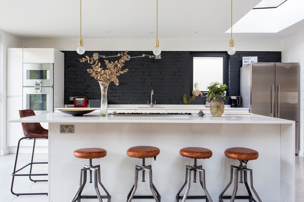 Inspiration for a mid-sized contemporary single-wall concrete floor and gray floor kitchen remodel in London with an undermount sink, flat-panel cabinets, black backsplash, brick backsplash, stainless steel appliances, an island and white countertops