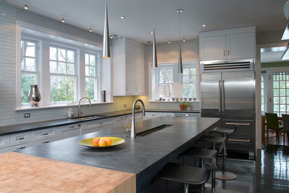 Large trendy eat-in kitchen photo in Philadelphia with white cabinets, white backsplash, stainless steel appliances, glass tile backsplash, an island, an undermount sink, soapstone countertops, black countertops and shaker cabinets
