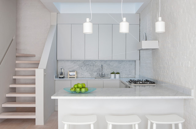 This is an example of a small contemporary l-shaped kitchen in London with a submerged sink, flat-panel cabinets, stone slab splashback, light hardwood flooring and a breakfast bar.