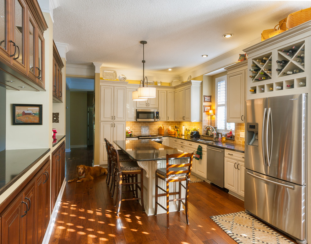 Example of a classic l-shaped enclosed kitchen design in Jacksonville with a double-bowl sink, raised-panel cabinets, beige cabinets, beige backsplash and stainless steel appliances