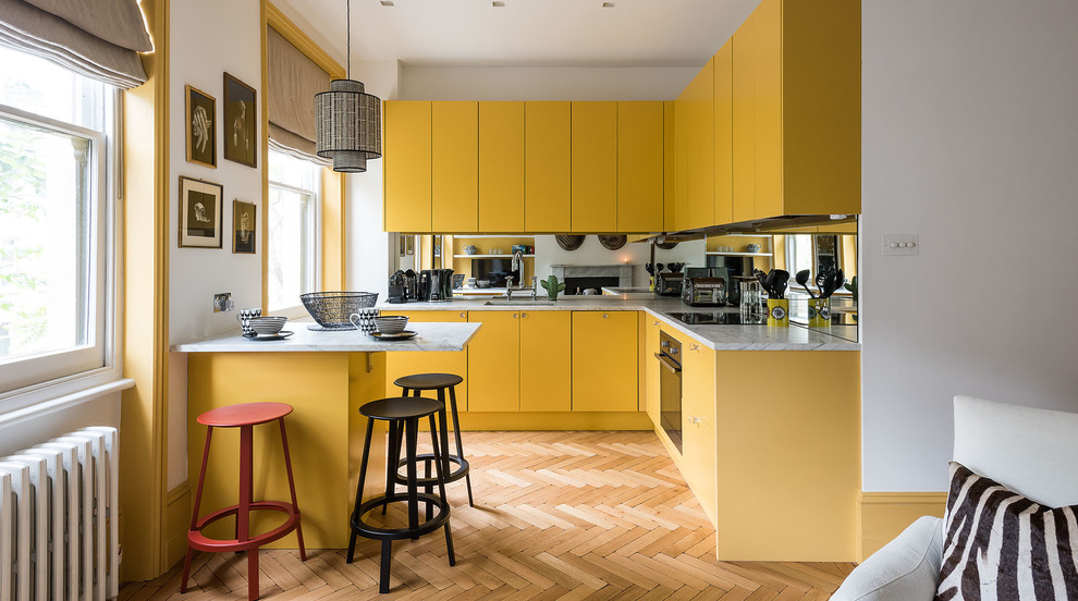 Example of a small danish l-shaped medium tone wood floor kitchen design in London with an undermount sink, flat-panel cabinets, yellow cabinets, mirror backsplash and a peninsula