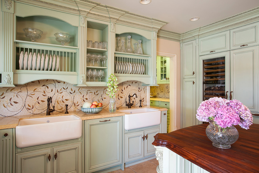 Inspiration for a timeless kitchen remodel in Los Angeles with a farmhouse sink, recessed-panel cabinets, green cabinets, beige backsplash, mosaic tile backsplash, paneled appliances and an island