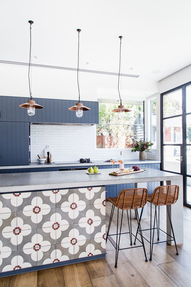 This is an example of a beach style galley kitchen in Melbourne with blue cabinets, concrete benchtops, white splashback, light hardwood floors and with island.