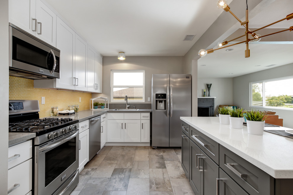 Example of a small minimalist l-shaped porcelain tile open concept kitchen design in San Diego with a drop-in sink, shaker cabinets, white cabinets, quartz countertops, yellow backsplash, mosaic tile backsplash, stainless steel appliances and an island