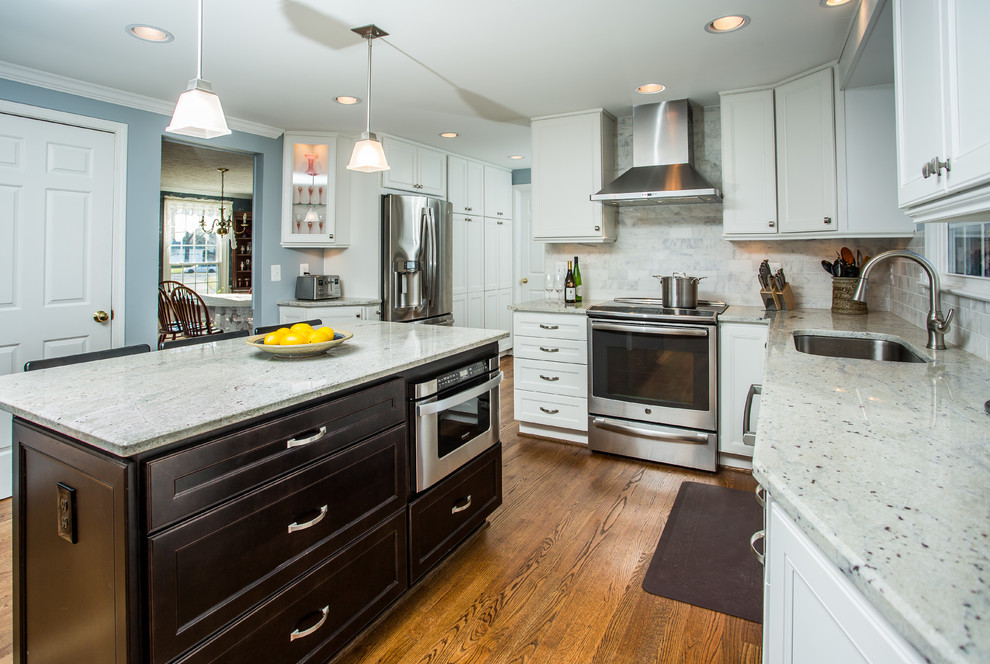 Inspiration for a contemporary l-shaped dark wood floor open concept kitchen remodel in DC Metro with a double-bowl sink, recessed-panel cabinets, white cabinets, granite countertops, beige backsplash, stone tile backsplash, stainless steel appliances and an island