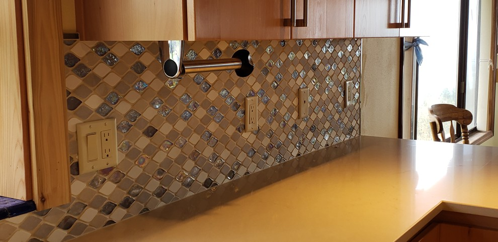 Example of a mid-sized transitional u-shaped laminate floor and beige floor eat-in kitchen design in Portland with a double-bowl sink, flat-panel cabinets, light wood cabinets, quartzite countertops, multicolored backsplash, glass tile backsplash, paneled appliances, an island and beige countertops