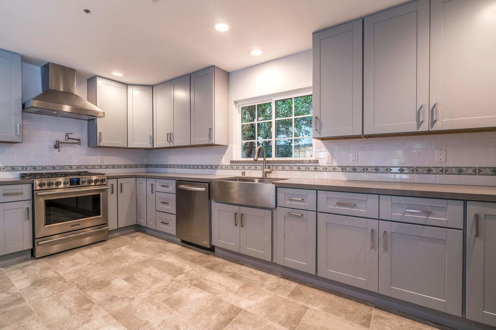 Mid-sized transitional u-shaped porcelain tile and gray floor eat-in kitchen photo in Orange County with a farmhouse sink, recessed-panel cabinets, gray cabinets, quartz countertops, white backsplash, subway tile backsplash, stainless steel appliances, an island and white countertops